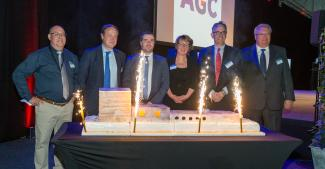 AGC and public officials in front of the cake in the form of a complete float line